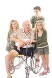 Nipoti con il nonno di handicap nel wheelch immagini stock