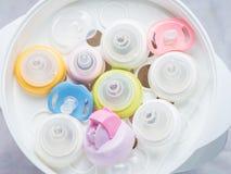 Nippel teethers und Milchflaschen im Dampfsterilisator und -trockner Lizenzfreies Stockbild