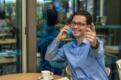 Nippender Kaffee des jungen Geschäftsmannes und Ablesenzeitung am Café stockfotografie
