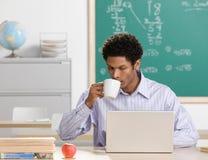 Nippender Kaffee des Lehrers und Arbeiten an Laptop Stockbilder