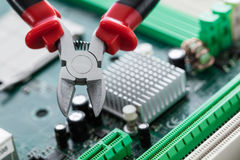 Nippers close-up. On computer circuit board background Stock Images
