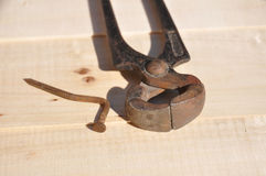Nippers and nail. Rusty old nippers and curved nail laying on wooden surface, close up Royalty Free Stock Photos