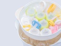 Nipplar och mjölkar flaskan i ångasteriliseringsapparat och tork Arkivfoton