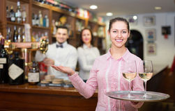 Nippy with beverages and bar crew. Cheerful nippy with beverages and bar crew at background Royalty Free Stock Image
