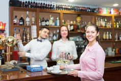 Nippy with beverages and bar crew. Smiling brunette nippy with beverages and bar crew at background Stock Image