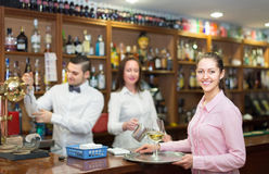 Nippy with beverages and bar crew. Smiling european nippy with beverages and bar crew at background Royalty Free Stock Photography