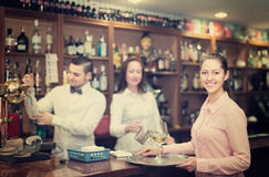 Nippy with beverages and bar crew. Smiling european nippy with beverages and bar crew at background Royalty Free Stock Photos