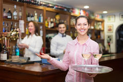 Nippy with beverages and bar crew. Smiling happy nippy with beverages and bar crew at background Stock Photo
