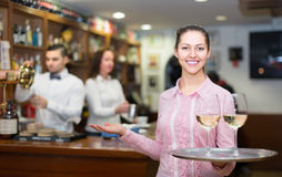 Nippy with beverages and bar crew. Smiling waitress with beverages and bar crew at background Stock Photo