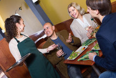 Nippy serving table with adults. Young nippy serving table with happy adults in restaurant Royalty Free Stock Photos