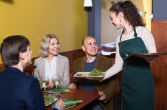 Nippy serving table with adults. Young spanish nippy serving table with happy adults in restaurant Royalty Free Stock Photography