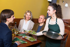 Nippy serving table with happy adults. Young nippy serving table with  adults in restaurant Royalty Free Stock Photos