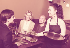 Nippy serving table with happy adults. Young nippy serving table with  adults in restaurant Stock Image