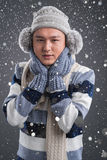 Nippy weather. Vertical portrait of a young man wearing in warm clothes because of the nippy snowy weather Royalty Free Stock Images