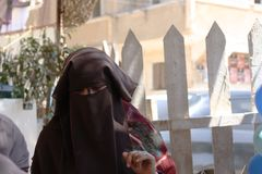 Niqabi woman veiled in souk or marketplace Stock Image