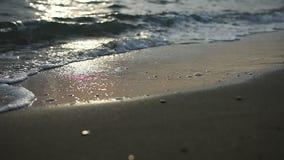 Nirvana na praia - cena idílico calma de um por do sol dourado sobre o mar, ondas que espirram lentamente na areia video estoque