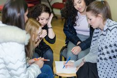 Girl draws on paper and team collaboration meeting start up. Female diversity young people studying working together. Nis, Serbia - February 14, 2019: Girl draws royalty free stock photo