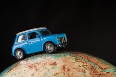 NIS, SERBIA - JANUARY 8 2018 Miniature figure toy car Mini Morris on geographical globe of earth on black background in studio. Miniature blue figure toy car Stock Image