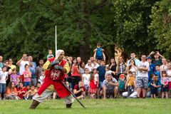 Medieval knight in the red suit with a sword shows knightly skills on at the international festival of knights