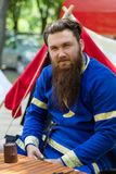 Portrait of a knight with a beard in a blue traditional suit sits. Nis, Serbia - June 15. 2019: Portrait of a knight with a beard in a blue traditional suit sits royalty free stock photo