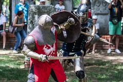 Two medieval knights fighting with hard weapon in armor in nature stock image
