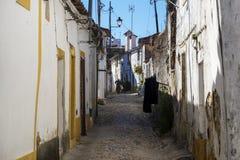 Woman walking along a narrow cobblestone street in the village of Nisa, Alentejo Stock Photography