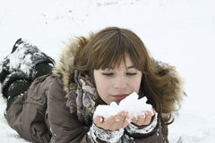 The nise girl lays with snow in hands Royalty Free Stock Images