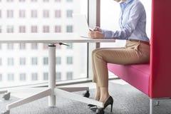 Niska sekcja bizneswoman używa laptop przy biurem podczas gdy siedzący fotografia stock