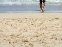 Niska sekcja bosy mężczyzny odprowadzenie w fale na piaskowatej plaży obrazy royalty free