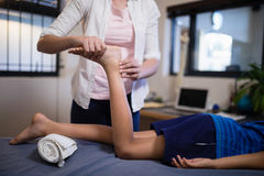 Niska sekcja chłopiec odbiorczy nożny masaż od młodego żeńskiego terapeuta obraz stock