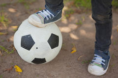 Niska sekcja chłopiec z nogą na futbolu przy parkiem zdjęcie royalty free