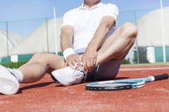 Niska sekcja dojrzała mężczyzny rozciągania noga podczas gdy siedzący na czerwonym tenisowym sądzie podczas lata zdjęcie royalty free