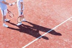 Niska sekcja dojrzali mężczyźni trząść ręki podczas gdy stojący na tenisowym sądzie podczas dopasowania zdjęcia stock