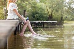 Niska sekcja dziewczyny obsiadanie z trawą na molu nad jeziorem zdjęcia stock
