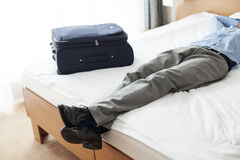 Niska sekcja młody biznesmena dosypianie obok walizki w pokoju hotelowym fotografia stock