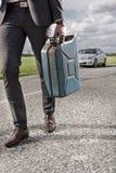 Niska sekcja młody biznesmena przewożenia gaz może z łamanym samochodem w tle przy wsią obrazy royalty free