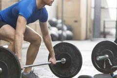 Niska sekcja oddanego mężczyzna podnośny barbell w crossfit gym fotografia royalty free