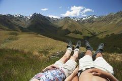 Niska sekcja pary lying on the beach W trawie górami zdjęcie royalty free