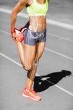 Niska sekcja sportsmenki rozciągania noga na śladzie obraz royalty free