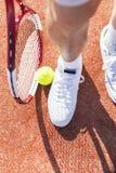 Niska sekcja starszego mężczyzny pozycja z tenisowym kantem i piłką na czerwień sądzie zdjęcia royalty free