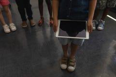 Niska sekcja trzyma cyfrową pastylkę w sali lekcyjnej dzieciak obraz royalty free