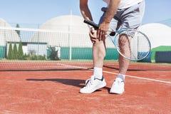 Niska sekcja trzyma tenisowego kant dojrzały mężczyzna podczas gdy cierpiący od kolano bólu na czerwonym tenisowym sądzie podczas obrazy stock
