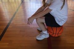 Niska sekcja uczennicy obsiadanie na koszykówce przy boiskiem do koszykówki zdjęcie stock