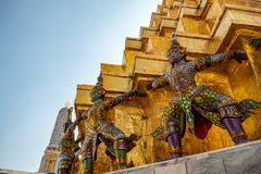 Niski kąt gigantyczne statuy na bazie złota pagoda w królewskiej świątyni w uroczystym pałac z jasnym niebieskiego nieba tłem zdjęcie stock