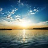 Niski pomarańczowy słońce w chmurach nad rzeką obrazy royalty free