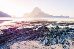 Niski przypływ z skałami w przodzie i na wschodzie słońca i zadziwiającym kształcie Cadlao wyspa w tle, el, Palawan zdjęcie royalty free