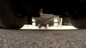 Niskiego kąta widok pod semi ciężarowym jeżdżeniem Kamera ustawia na ulicie z niektóre chwiejnością od ciężaru ciężarówka zbiory wideo