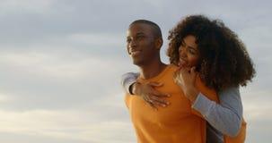 Niskiego kąta widok daje piggyback przejażdżce kobieta na plaży 4k amerykanin afrykańskiego pochodzenia mężczyzna zdjęcie wideo
