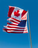 Niskiego kąta widok kanadyjczyk i flaga amerykańskie, obraz stock