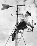 Niskiego kąta widok młoda kobieta naprawia pogodowego vane (Wszystkie persons przedstawiający no są długiego utrzymania i żadny n Obrazy Stock
